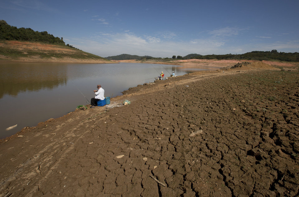 Photo - In this May 14, 2014 photo, people fish at the Jaguari dam, which is part of the Cantareira System, responsible for providing water to the Sao Paulo metropolitan area, in Braganca Paulista, Brazil. The worst drought in more than 80 years is hitting Sao Paulo, Brazil's largest city just as it prepares for the tens of thousands of foreigners expected at the tournament opener. (AP Photo/Andre Penner)