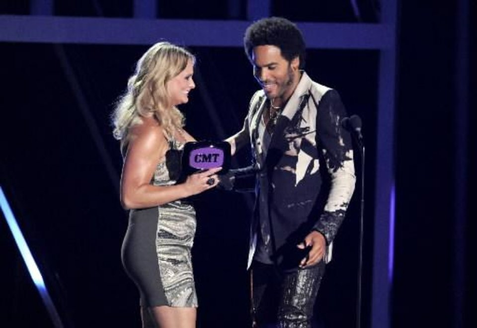 "Lenny Kravitz, right, presents the award for female video of the year to Miranda Lambert for ""Mama's Broken Heart"" at the 2013 CMT Music Awards at Bridgestone Arena on Wednesday, June 5, 2013, in Nashville, Tenn.  (AP)"