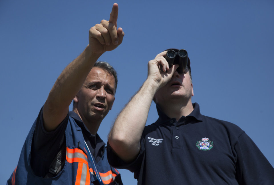 Photo - An Australian investigator, right, and his Dutch counterpart examines the area of the Malaysia Airlines Flight 17 plane crash in the village of Hrabove, Donetsk region, eastern Ukraine Friday, Aug. 1, 2014. The investigators from the Netherlands and Australia plus officials with the Organization for Security and Cooperation in Europe traveled from the rebel-held city of Donetsk in 15 cars and a bus to the crash site outside the village of Hrabove. Then they started setting up a base to work from at a chicken farm. (AP Photo/Dmitry Lovetsky)
