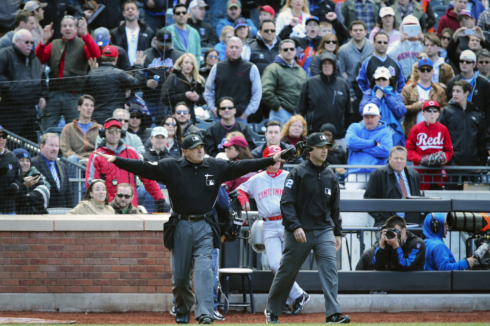 Photo - Umpire John Hirschbeck, left, rules the New York Mets center fielder Juan Lagares safe at second base after video replay overturned the call by umpire James Hoye, right, in the ninth inning of a baseball game against the Cincinnati Reds at Citi Field, Saturday, April 5, 2014, in New York. The Mets won 6-3. (AP Photo/John Minchillo)