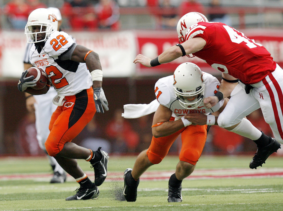 Photo - OSU's Dantrell Savage (22) carries the ball as quarterback Zac Robinson (11) blocks Nebraska's Ben Eisenhart (46) in the second quarter during the college football game between Oklahoma State University (OSU) and the University of Nebraska (NU) at Memorial Stadium in Lincoln, Neb., Saturday, October 13, 2007. By Nate Billings, The Oklahoman