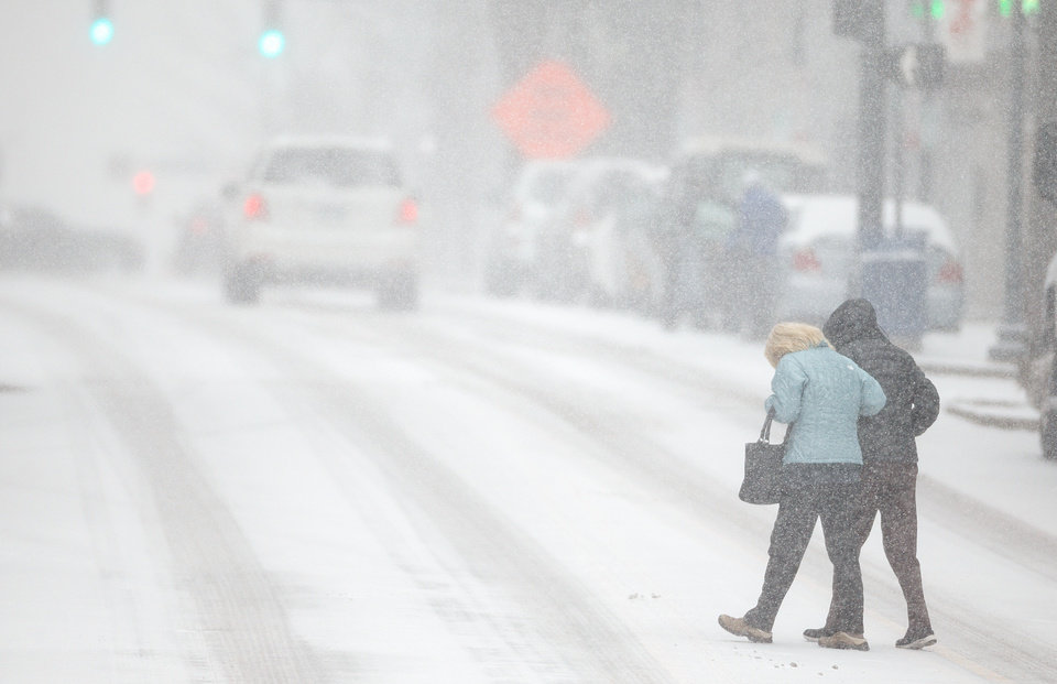Photo - Pedestrians support each other as they cross S. Elm St. during a snow storm, Wednesday, Feb. 12, 2014 in Greensboro, N.C. As a third winter storm in as many days slammed into North Carolina, commutes that typically took minutes turned into hours-long ordeals. The National Weather Service issued a winter storm warning lasting into Thursday covering 95 of the state's 100 counties. (AP Photo/News & Record, Jerry Wolford)