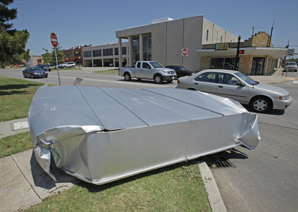 Debris from Tuesday's severe thunderstorm blown from the roof of the Pioneer Library lies next to the street  on Wednesday, June 15, 2011, in Norman, Okla.  Photo by Steve Sisney, The Oklahoman