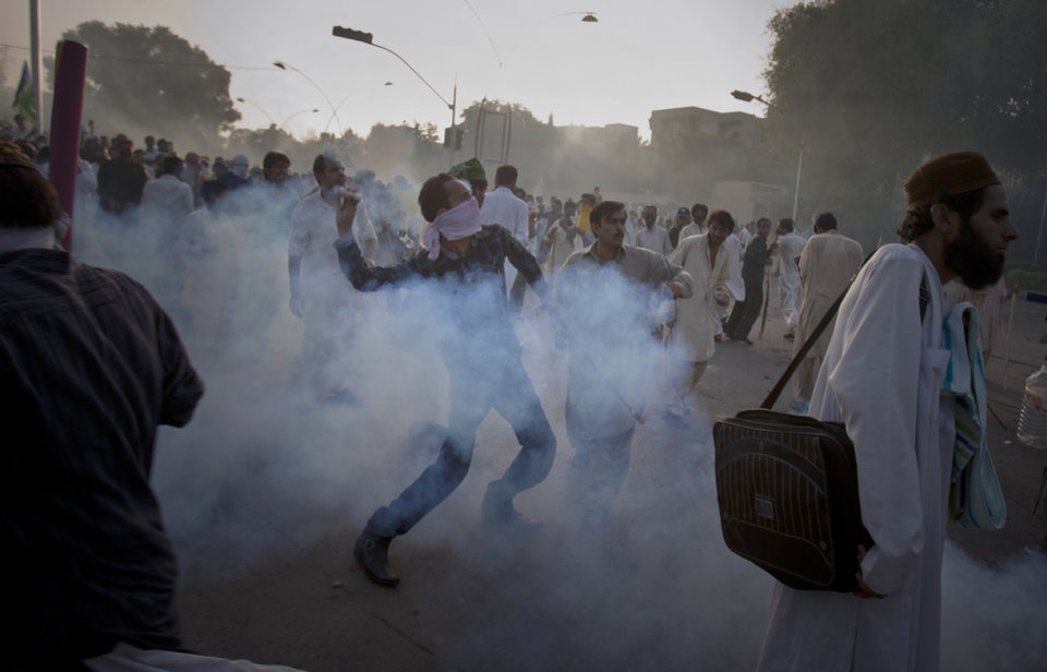 "A Pakistani protestor hurls back a tear gas canister fired by police during clashes that erupted as the demonstrators tried to approach the U.S. embassy in Islamabad, Pakistan, Friday, Sept. 21, 2012. Over a dozen people were killed as tens of thousands protested against the film around the country after the government encouraged peaceful protests and declared a national holiday — ""Love for the Prophet Day."" Demonstrations turned violent in several Pakistani cities. AP photo"