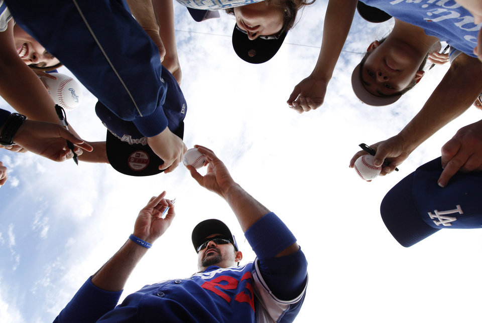 Photo - Los Angeles Dodgers first baseman Adrian Gonzalez signs autographs before an exhibition baseball game against the Chicago White Sox in Glendale, Ariz., Friday, Feb. 28, 2014. (AP Photo/Paul Sancya)