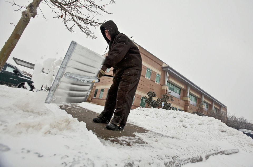Photo - John McBride uses a snow shovel to clear the sidewalks and parking lots of ice and snow at Integris Canadian Valley Hospital on Friday, Jan. 29, 2010, in Yukon, Okla.   Photo by Chris Landsberger, The Oklahoman