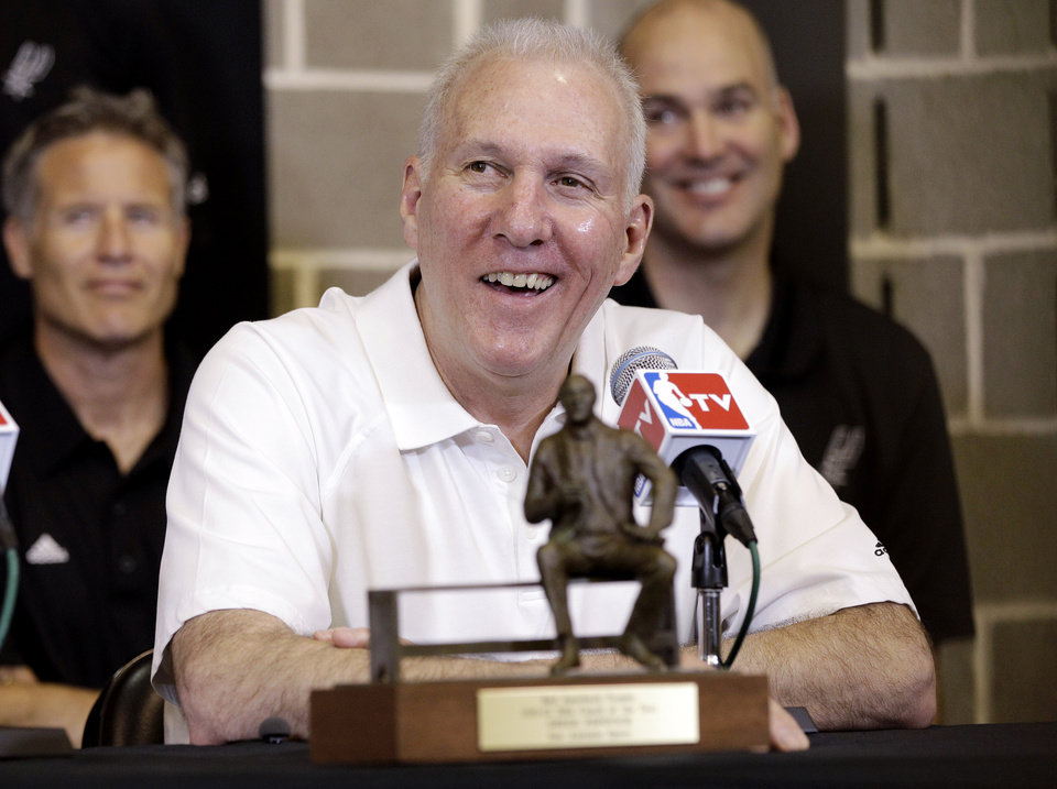Photo -   San Antonio Spurs head basketball wldcoach Gregg Popovich sits behind the Red Auerbach trophy after he was named the NBA's Coach of the Year during a news conference at the team's basketball practice facility, Tuesday, May 1, 2012, in San Antonio. (AP Photo/Eric Gay)