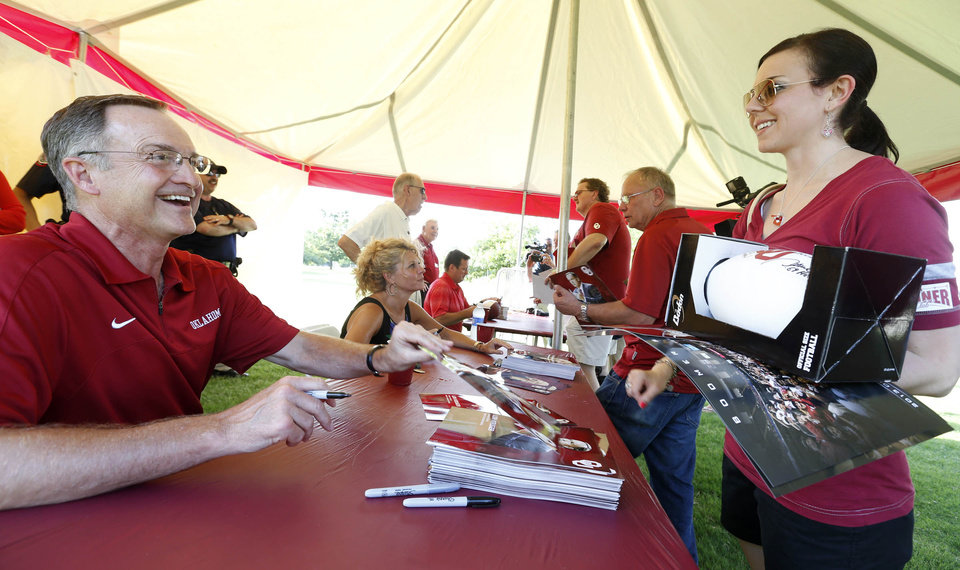 Photo -                    OU basketball coach Lon Kruger, left, greets fan Candice Hall of Tulsa during Thursday's Sooner Caravan stop.                     Photo by JAMES GIBBARD, Tulsa World