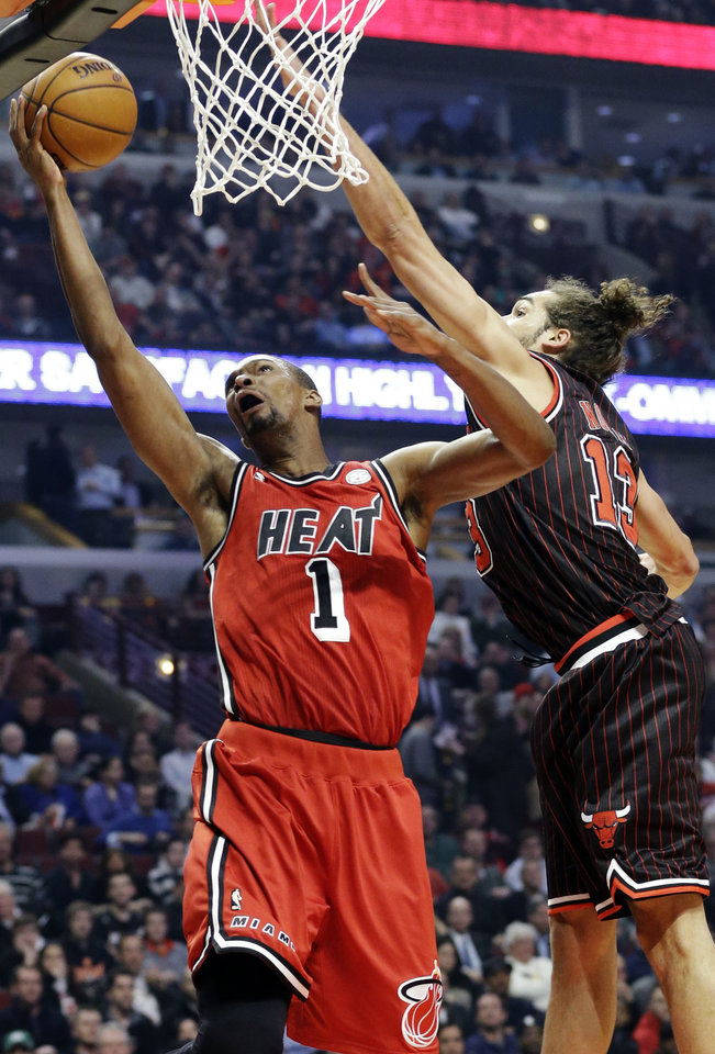 Photo - Miami Heat center Chris Bosh (1) drives to the basket against Chicago Bulls center Joakim Noah during the first half of an NBA basketball game in Chicago, Thursday, Feb. 21, 2013. (AP Photo/Nam Y. Huh)