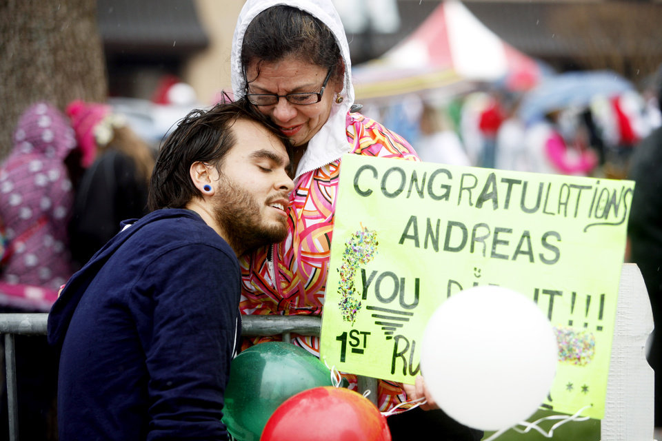 Photo -  After completing the race, Andreas Nowag, 23, hugs his mom Minerva Nowag at the finish line of the Redbud Classic at Nichols Hills Plaza in Nichols Hills, OK, Sunday, April 6, 2014. Photo by KT King, The Oklahoman