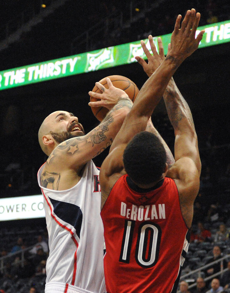 Photo - Atlanta Hawks' Pero Antic (6) shoots over Toronto Raptors' DeMar DeRozan (10) in the first half of their NBA basketball game Tuesday, March 18, 2014, in Atlanta. (AP Photo/David Tulis)