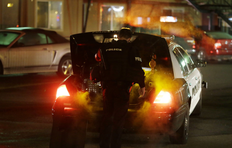 Photo - A Tukwila Police officer puts gear in his trunk after returning to his car near the scene of an overnight shooting that left five people dead, Monday, April 22, 2013, at an apartment complex in Federal Way, Wash. (AP Photo/Ted S. Warren)