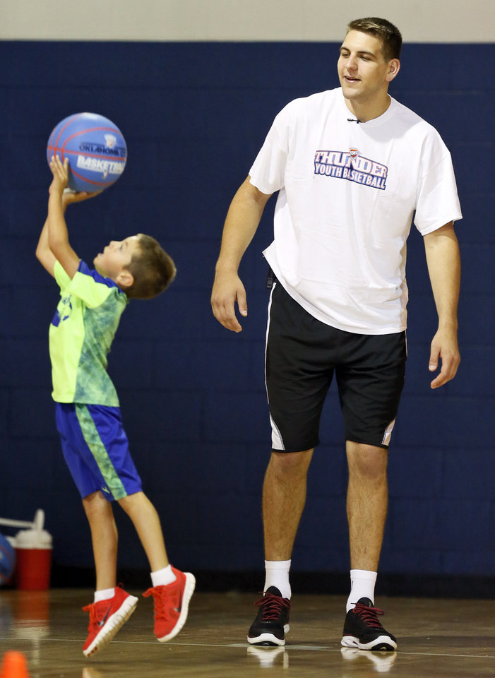 Photo - Thunder player Mitch McGary watches a camper take a shot during a visit to Thunder Youth Basketball Camp at Casady School in Oklahoma City, Wednesday, July 16, 2014. Photo by Nate Billings, The Oklahoman