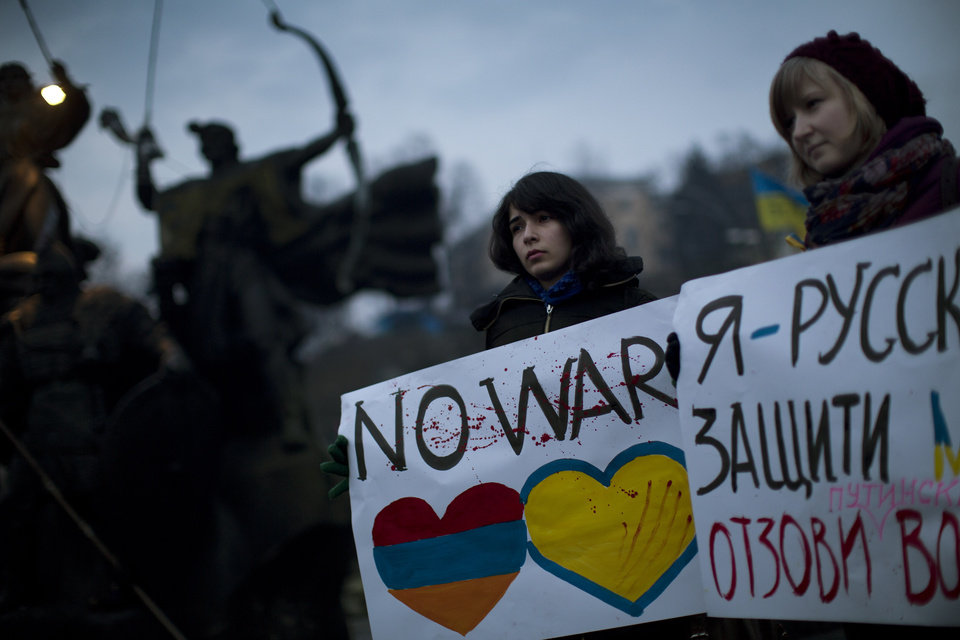 Photo - Ukrainian Maria, 23, right, and Vanui, 22, hold posters against Russia's military intervention in Crimea, in Kiev, Ukraine, Sunday, March 2, 2014. Russia's parliament approved a motion to use the country's military in Ukraine after a request from President Vladimir Putin as protests in Russian-speaking cities turned violent Saturday, sparking fears of a wide-scale invasion. The poster in the right side reads in Ukrainian: