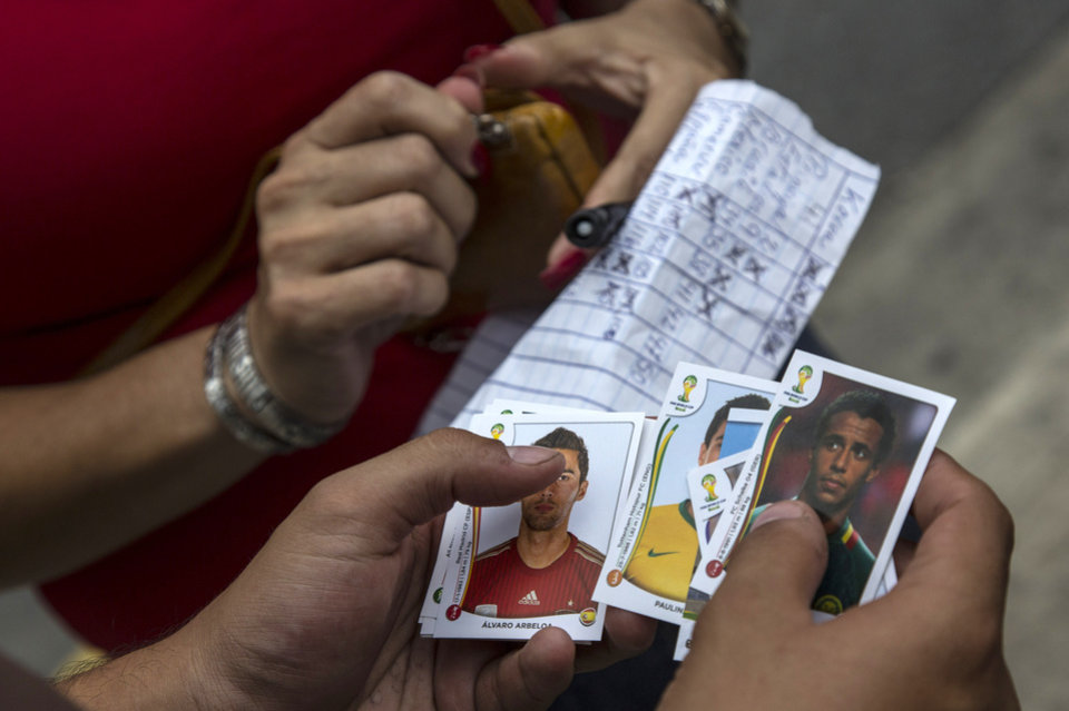 Photo - A woman buys stickers of soccer players to complete her World Cup sticker album at a meeting of collectors in Caracas, Venezuela, Saturday, June 21, 2014. TV personalities, and professional collectors can all be found at ad-hoc trading centers, searching for the more than 600 stickers that constitute a complete 2014 collection. Traders say the hobby provides a connection to the tournament, and a distraction from the troubles that have recently wracked the country. (AP Photo/Ramon Espinosa)