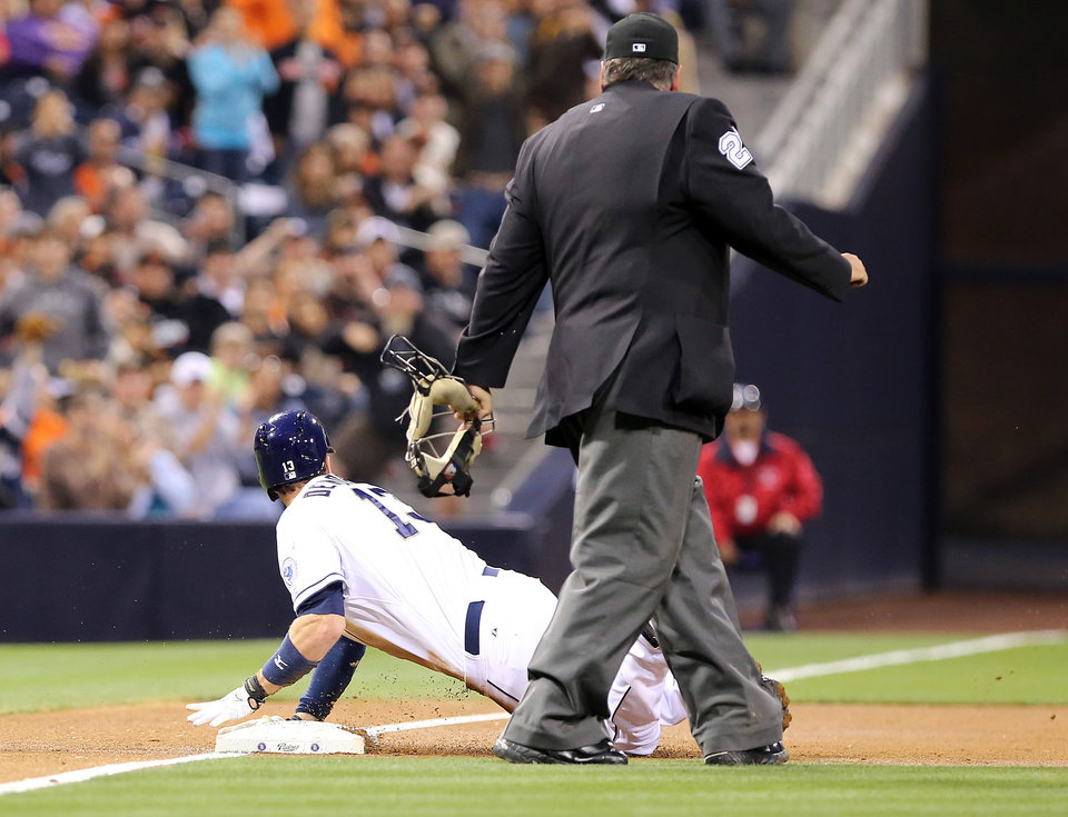 Photo - San Diego Padres' Chris Denorfia, left, slides in safely on a triple against the San Francisco Giants in the first inning of a baseball game on Friday, April 18, 2014, in San Diego. (AP Photo/Don Boomer)