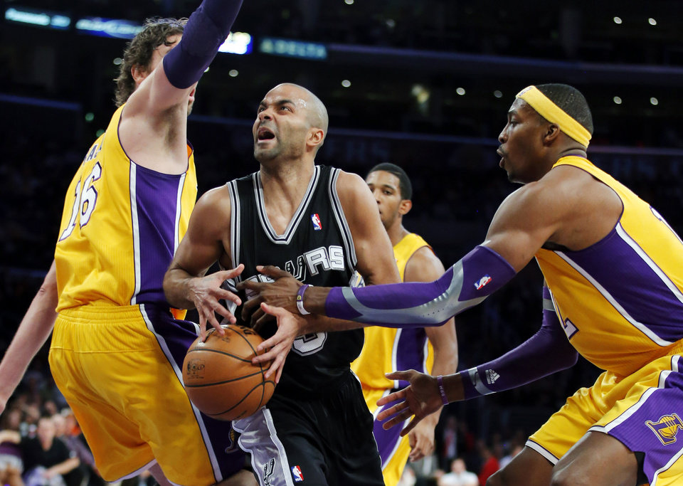 San Antonio Spurs' Tony Parker, center, of France, is defended by Los Angeles Lakers' Dwight Howard, right, and Pau Gasol, of Spain, in the first half of an NBA basketball game in Los Angeles, Tuesday, Nov. 13, 2012. (AP Photo/Jae C. Hong)