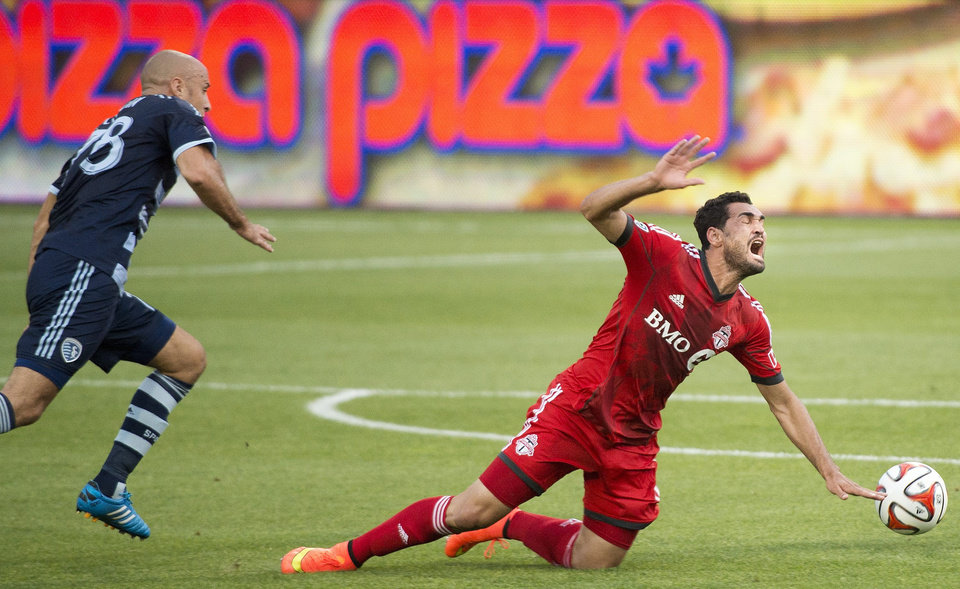 Photo - Toronto FC forward Gilberto, right, gets tripped up by Sporting Kansas City midfielder Victor Munoz during the first half of an MLS soccer game Saturday, July 26, 2014, in Toronto. (AP Photo/The Canadian Press, Nathan Denette)