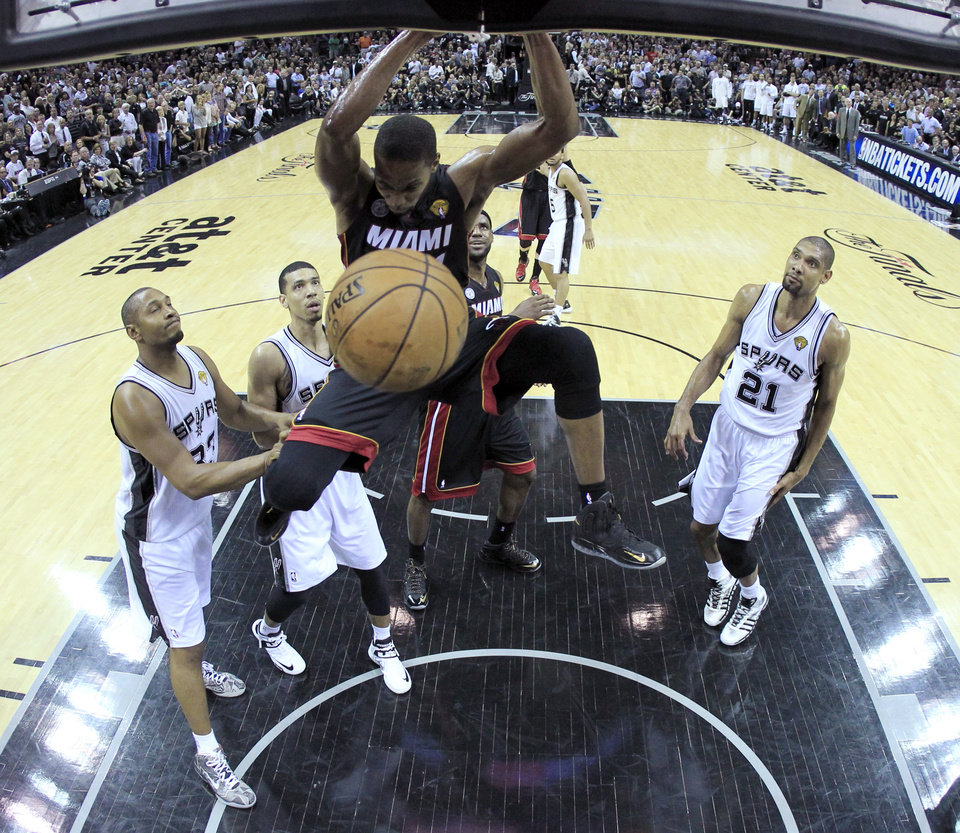 Photo - Miami Heat's Chris Bosh (1) dunks against the San Antonio Spurs during the first half at Game 4 of the NBA Finals basketball series, Thursday, June 13, 2013, in San Antonio. (AP Photo/Lucy Nicholson, Pool)
