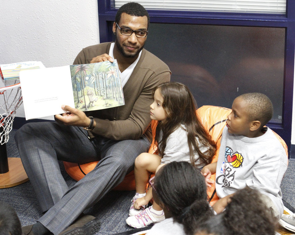 Photo - Oklahoma City Thunder's Lazar Hayward reads to children at the opening of the NBA Cares Learn & Play Center at the City Rescue Mission in Oklahoma City. Photo By Steve Gooch, The Oklahoman  Steve Gooch - The Oklahoman