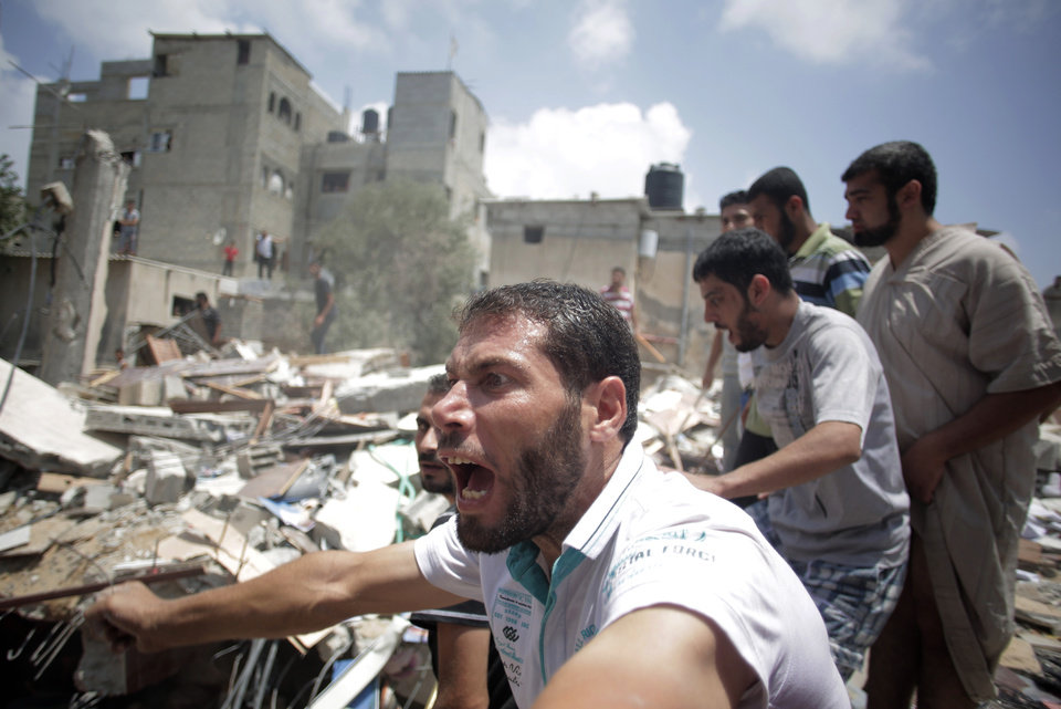 Photo - A Palestinian overcome by emotion watches rescuers carry a body from the rubble of a house which was destroyed by an Israeli missile strike, in Gaza City, Monday, July 21, 2014. On Sunday, the first major ground battle in two weeks of Israel-Hamas fighting exacted a steep price, killing scores Palestinians and over a dozen Israeli soldiers and forcing thousands of terrified Palestinian civilians to flee their devastated Shijaiyah neighborhood, which Israel says is a major source for rocket fire against its civilians. (AP Photo/Khalil Hamra)