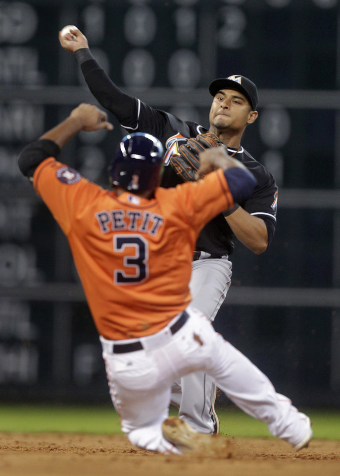 Photo - Miami Marlins second baseman Donovan Solano tags out Houston Astros Gregorio Petit (3) and throws to first to complete a double play on Jose Altuve during the third inning of a baseball game, Friday, July 25, 2014, in Houston. (AP Photo/Patric Schneider)