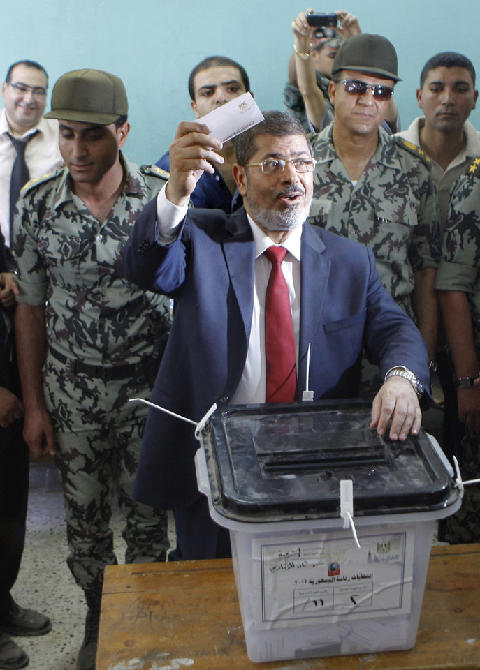 Photo -   FILE - In this Saturday, June 16, 2012 file photo, Egyptian presidential candidate Mohammed Morsi waves his ballot as he prepares to cast his vote at a polling station in Zagazig, 63 miles (100 kilometers) northeast of Cairo, Egypt. The Muslim Brotherhood has declared that its candidate, Mohammed Morsi, won Egypt's presidential election, early Monday, June 18, 2012. (AP Photo/Amr Nabil, File)