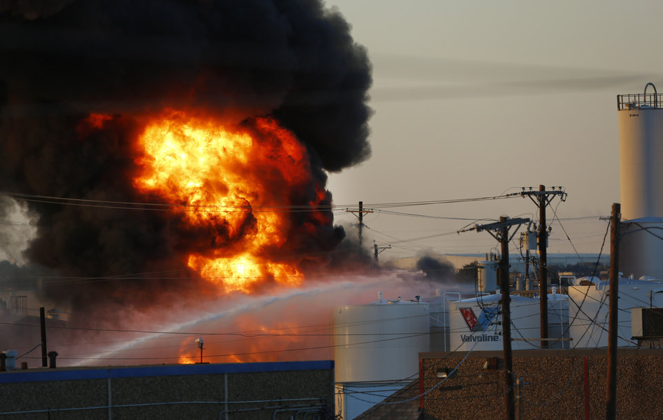 Photo -   Fire and smoke rise as Dallas and Garland fire crews pour water onto storage tanks near where a chemical fire burns off at the Nexeo Solutions plant in Garland, Texas, on Friday, Nov. 16, 2012. Fire Capt. Merrill Balanciere says it's still unclear what caused the fire, but the flames were fueled by highly flammable toluene and methanol. All 41 workers who were at the plant at the time of the fire are safe. (AP Photo/The Dallas Morning News, Tom Fox) MANDATORY CREDIT; MAGS OUT; TV OUT; INTERNET OUT; AP MEMBERS ONLY