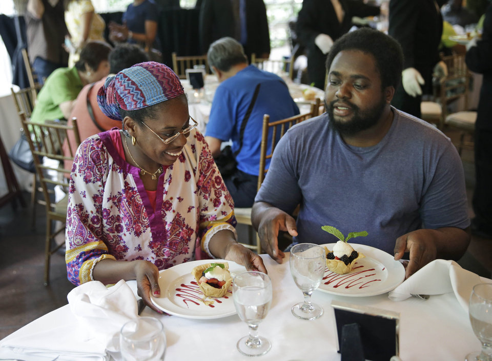 Photo - Sharon Robinson, left, and Roy Gantt, both residents of the New York City Rescue Mission, look over their just served desserts at The Loeb Boathouse restaurant in New York, Wednesday, June 25, 2014.  Recycling magnate Chen Guangbiao,  known for his sometimes eccentric gestures served up a fancy lunch Wednesday to hundreds of homeless New Yorkers at a Central Park restaurant and serenaded them with