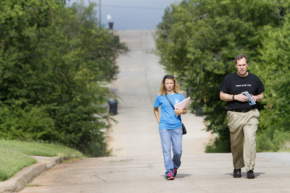 Christy Watson, communications director for the Foundation for Oklahoma City Public Schools, and schools Superintendent Karl Springer walk door to door, asking parents to enroll students in Thelma R. Parks Elementary School. PHOTO BY STEVE GOOCH, THE OKLAHOMAN Steve Gooch - The Oklahoman