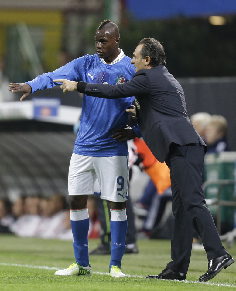 Photo -   Italy coach Cesare Prandelli, right, gives instructions to forward Mario Balotelli during a World Cup Group B qualifying soccer match between Italy and Denmark, in Milan, Italy, Tuesday, Oct.16, 2012. (AP Photo/Luca Bruno)