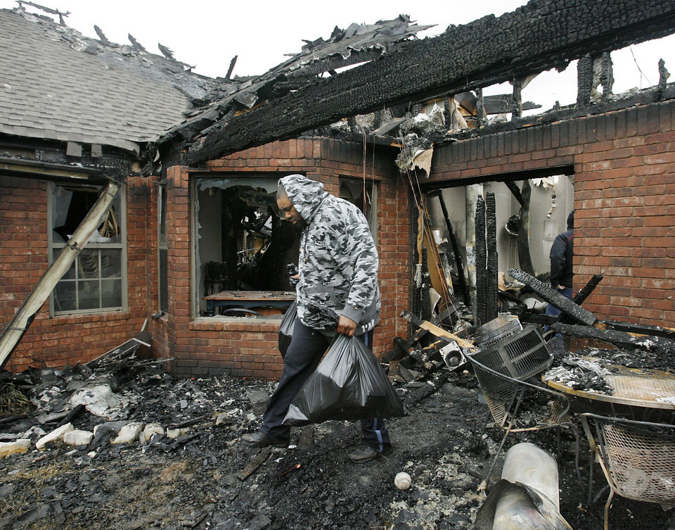 A friend carries bags of personal belongings from the home of Nathan and Sammetra Christman while helping salvage items from their home at 2040 Westbury St. in the Oakwood East Royale neighborhood. The home was destroyed in Thursday\'s wildfires. Photo by Jim Beckel, The Oklahoman