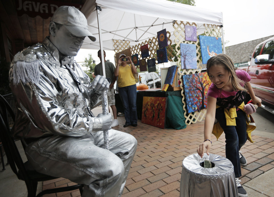 Right: Isabella Burnner, 10, of Edmond, gives a tip to the Silver Man during the Downtown Edmond Fall Art Crawl. The Art Crawl is sponsored by the Downtown Edmond Business Association.