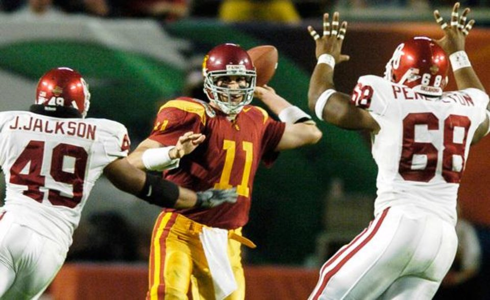 Miami, Florida - January 4, 2005. University of Oklahoma (OU) Sooners vs. University of Southern California (USC) Trojans college football in the Orange Bowl BCS National Championship at Pro Player Stadium. USC quarterback Matt Leinart (11) throws against Oklahoma's Jonathan Jackson (49) and Carl Pendelton (68) in the third quarter.  By Steve Sisney/The Oklahoman