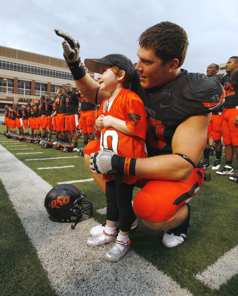 Taylor Brandt and Cooper Bassett sing the OSU alma mater and wave at fans after last season�s win over Kansas. The big football player and the tiny first-grader seem an unlikely pair, but their personalities are a perfect match.  PHOTO BY STEVE SISNEY, The Oklahoman Archives