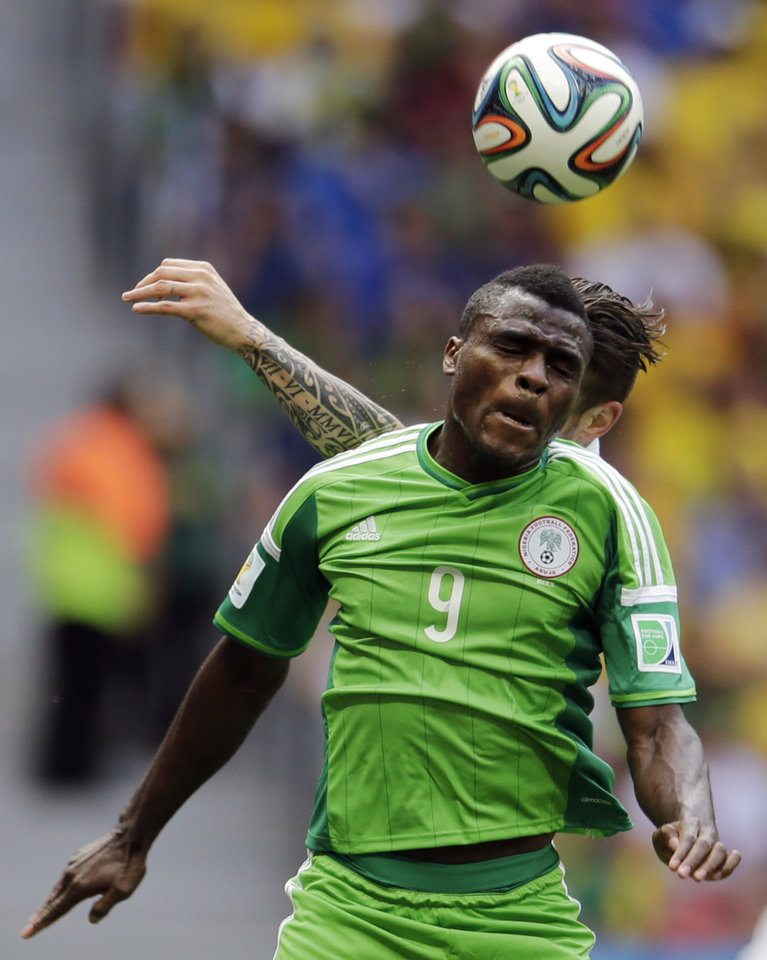 Photo - Nigeria's Emmanuel Emenike (9) heads the ball against France's Olivier Giroud during the World Cup round of 16 soccer match between France and Nigeria at the Estadio Nacional in Brasilia, Brazil, Monday, June 30, 2014. (AP Photo/Petr David Josek)