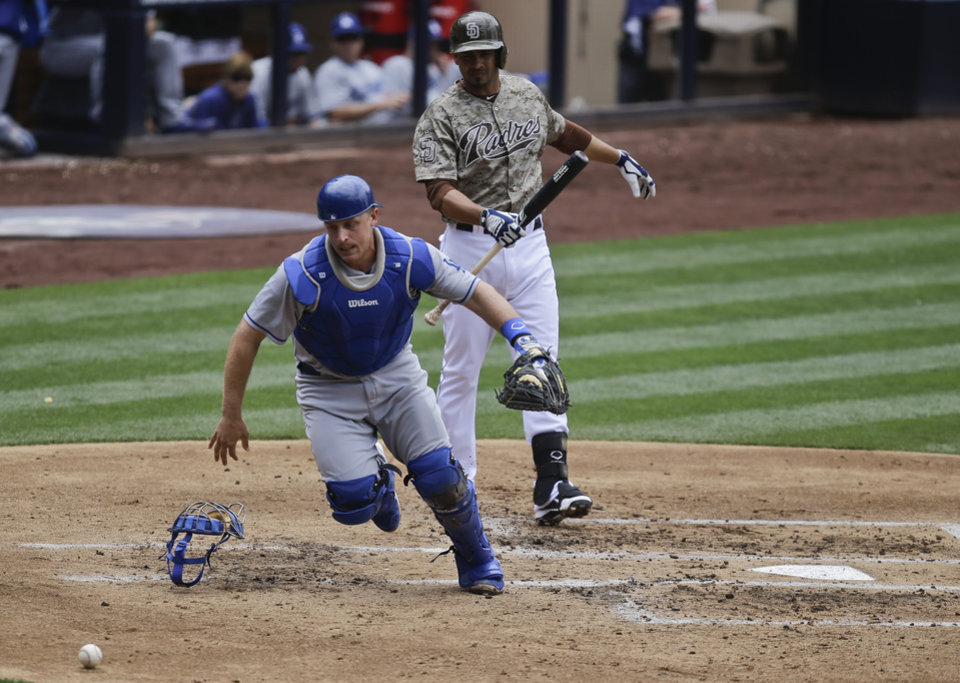 Photo - Los Angeles Dodgers catcher Tim Federowicz chases down a wild pitch as a San Diego Padres' baserunner advances during the second inning of a baseball game in San Diego, Sunday, June 23, 2013. The Padres batter is Jesus Guzman.  (AP Photo/Lenny Ignelzi)