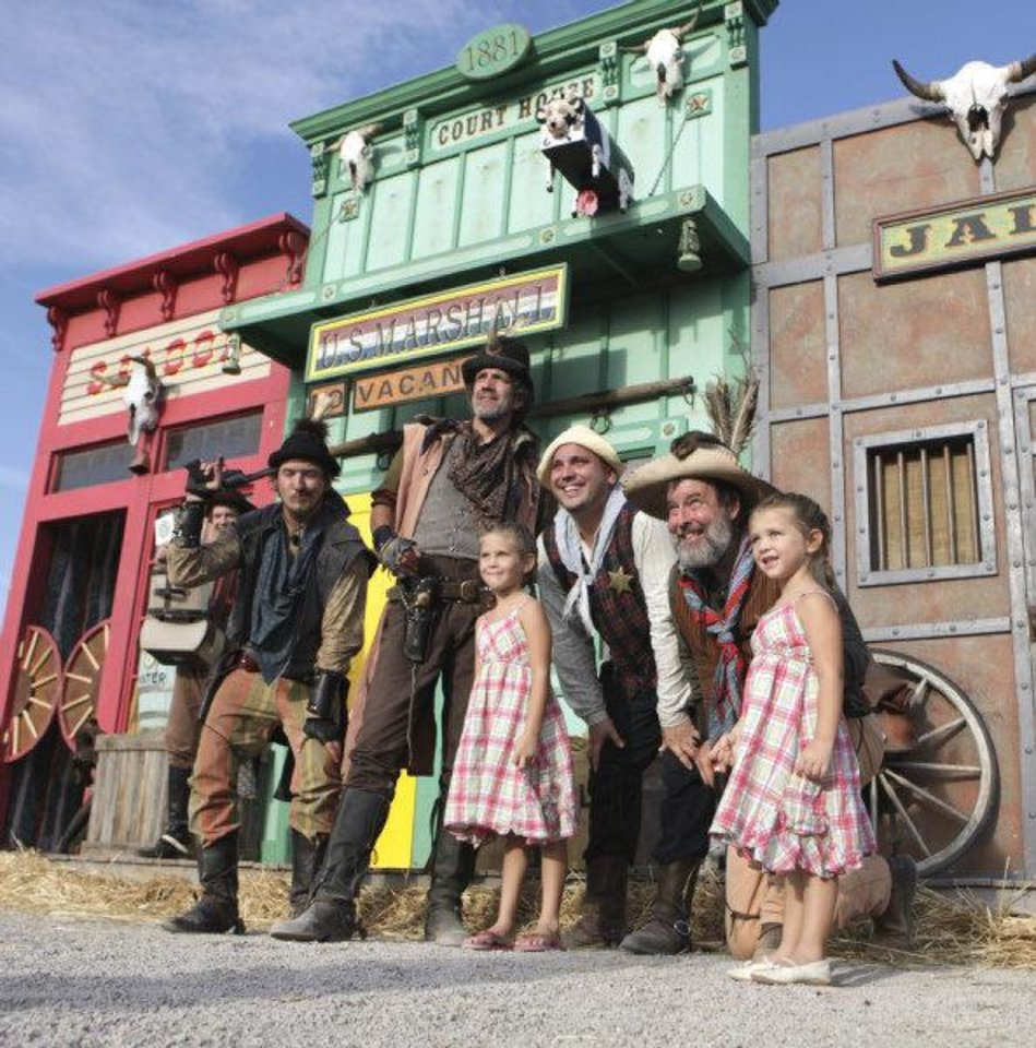 Photo - Bubba (Parker Hendricks), Bad Bob (Ron Cameron), Leon P. Jones (Mike Lee) and Hop-a-long Casually (Mike Walker) pose with audience members Addie (5) and Storie (3) Sangree of Oklahoma City after a performance of ShenaniGuns Comedy Wild West Show at the Oklahoma State Fair. Photo by Steve Sisney, The Oklahoman  STEVE SISNEY - THE OKLAHOMAN