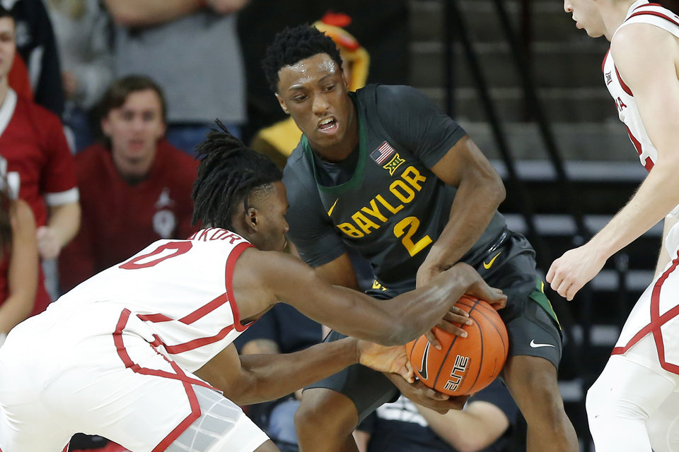 Photo - Oklahoma's Victor Iwuakor (0) fights for the ball with Baylor's Devonte Bandoo (2) during a men's NCAA basketball game between the University of Oklahoma Sooners (OU) and the Baylor Bears at the Lloyd Noble Center in Norman, Okla., Tuesday, Feb. 18, 2020. [Bryan Terry/The Oklahoman]