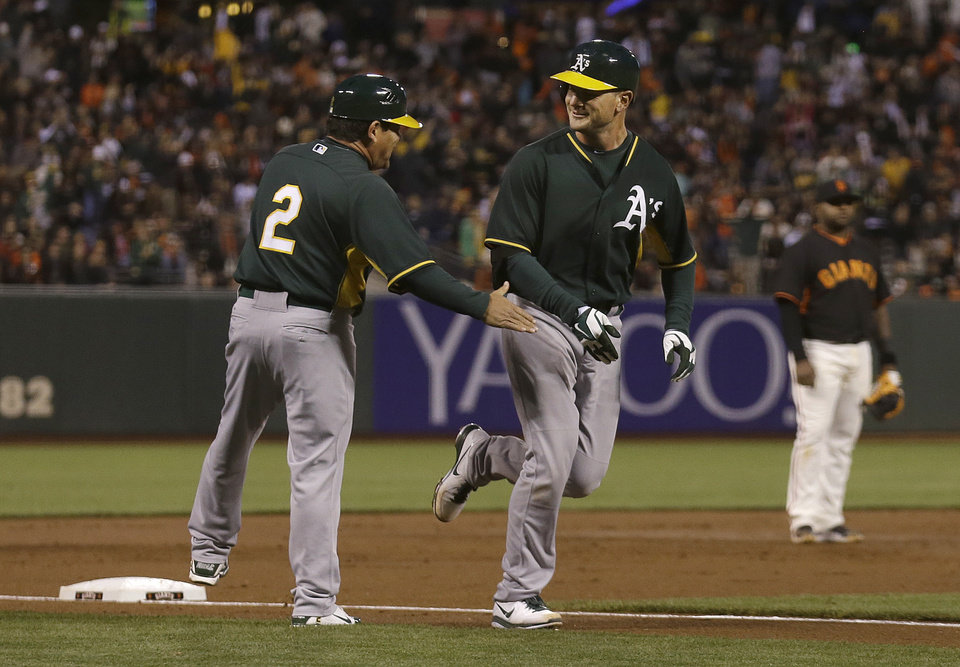 Photo - Oakland Athletics' John Jaso, center, is congratulated by third base coach Mike Gallego (2) after hitting a solo home run off San Francisco Giants pitcher Tim Lincecum during the third inning of an exhibition baseball game in San Francisco, Friday, March 28, 2014. (AP Photo/Jeff Chiu)