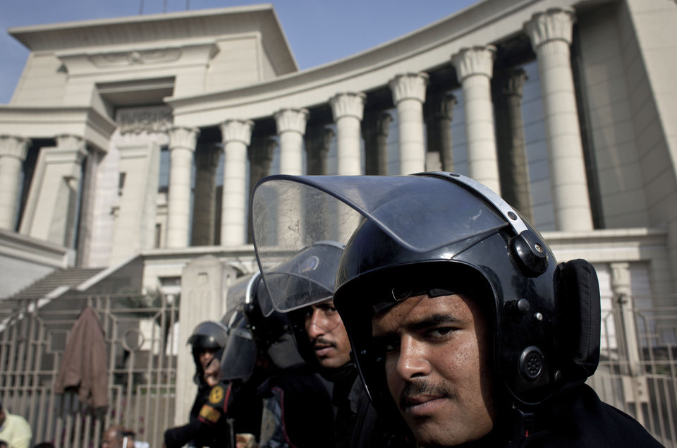 Photo - Riot policemen stand guard in front of Egypt's top court during a protest for supporters of Egyptian President Mohammed Morsi, unseen, in Cairo, Egypt, Monday, Dec. 3, 2012. The Egyptian president's top legal adviser says the country's election commission has begun preparations for the referendum on Dec. 15 on a highly contentious draft constitution. (AP Photo/Nasser Nasser)