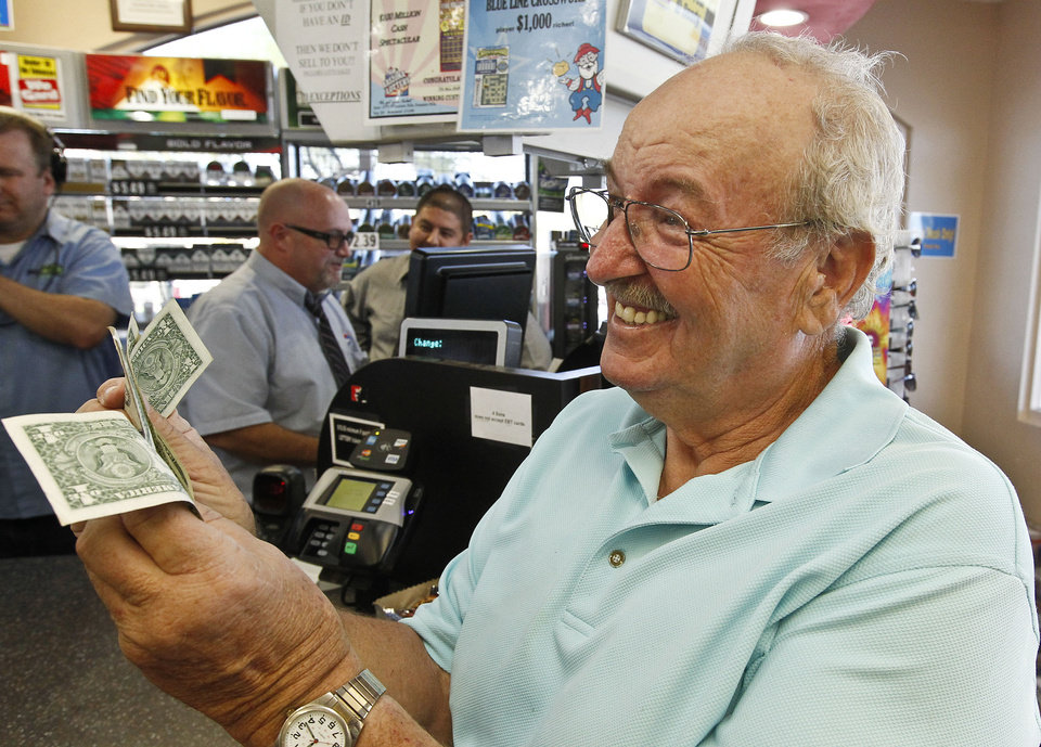 Photo - Wes Prinzen, of Fountain Hills, Ariz., smiles as he takes away his modest $4 winnings, at a 4 Sons Food Store where one of the winning tickets in the $579.9 million Powerball jackpot was purchased, Nov. 29, 2012, in Fountain Hills, Ariz. (AP Photo/Ross D. Franklin)