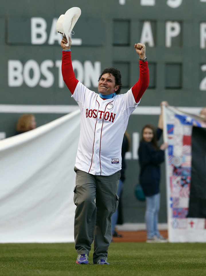 Photo - Boston Marathon bombing hero Carlos Arredondo waves to the crowd as he walks onto the field at Fenway Park during ceremonies marking the one-year anniversary of the bombing before a baseball game between the Boston Red Sox and the Baltimore Orioles in Boston, Sunday, April 20, 2014. (AP Photo/Michael Dwyer)