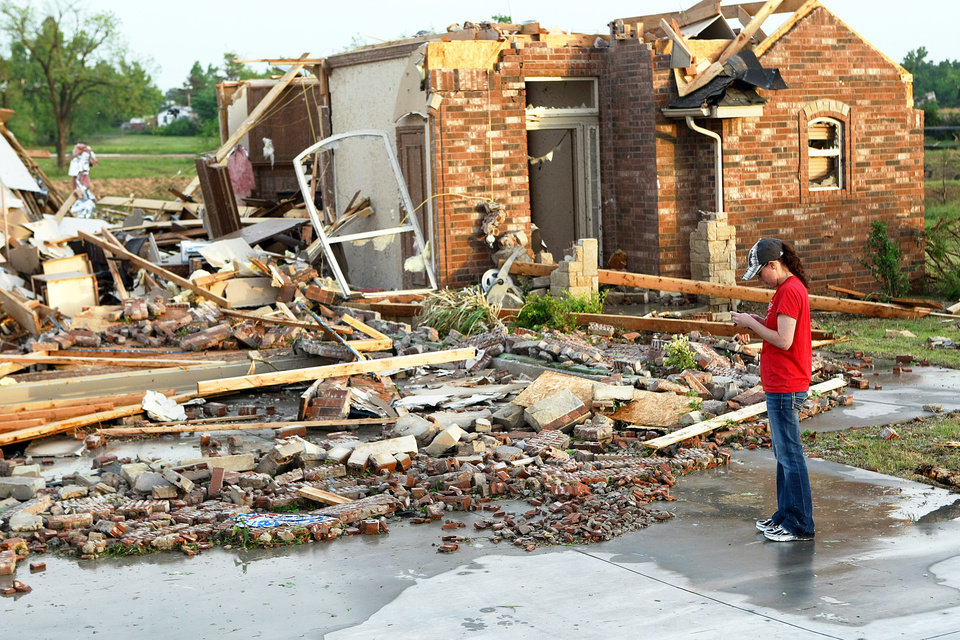 Ann Powell calls her insurance company while standing in front of what is left of her house, just south of Harrah Road and Reno on Monday evening after tornadoes ripped through the area. Powell moved to Oklahoma about a year ago from California. PHOTO BY HUGH SCOTT, THE OKLAHOMAN
