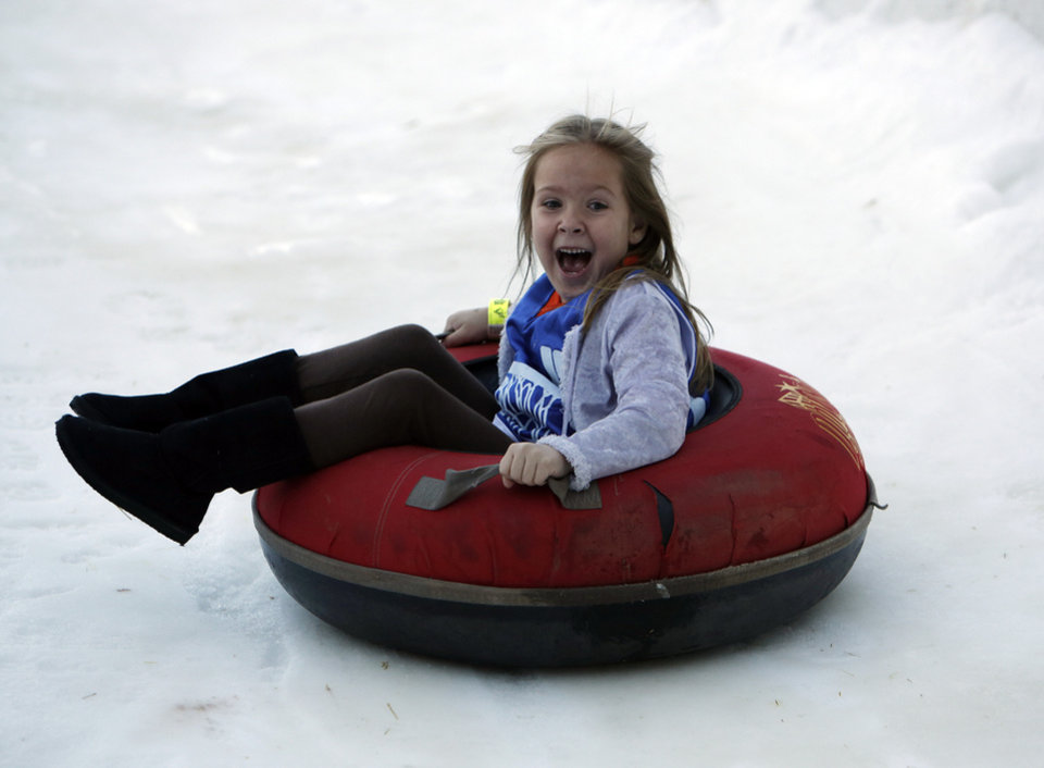 Georgia Hope VanMeter, 5, of Midwest City, tubes down a snow slope at Chickasaw Bricktown Ballpark in Oklahoma City, Saturday, Nov. 24, 2012.  Photo by Garett Fisbeck, The Oklahoman