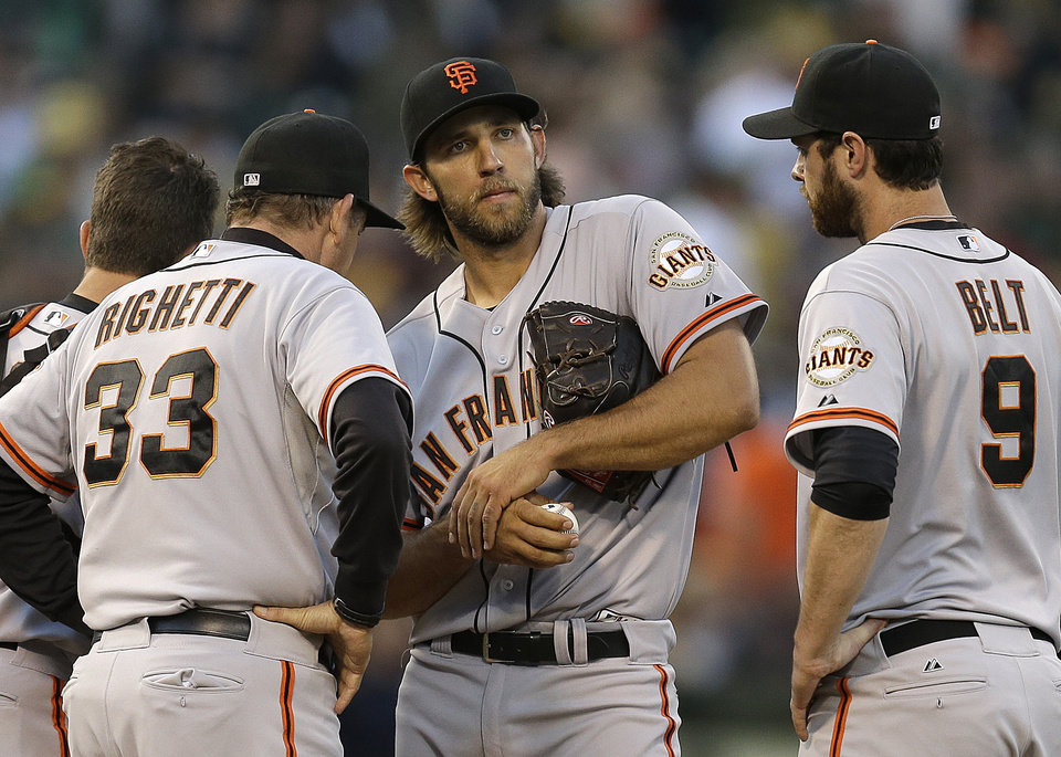 Photo - San Francisco Giants' Madison Bumgarner, center, is visited by pitching coach Dave Righetti (33) and Brandon Belt (9)  in the third inning of a baseball game against the Oakland Athletics Tuesday, July 8, 2014, in Oakland, Calif. (AP Photo/Ben Margot)
