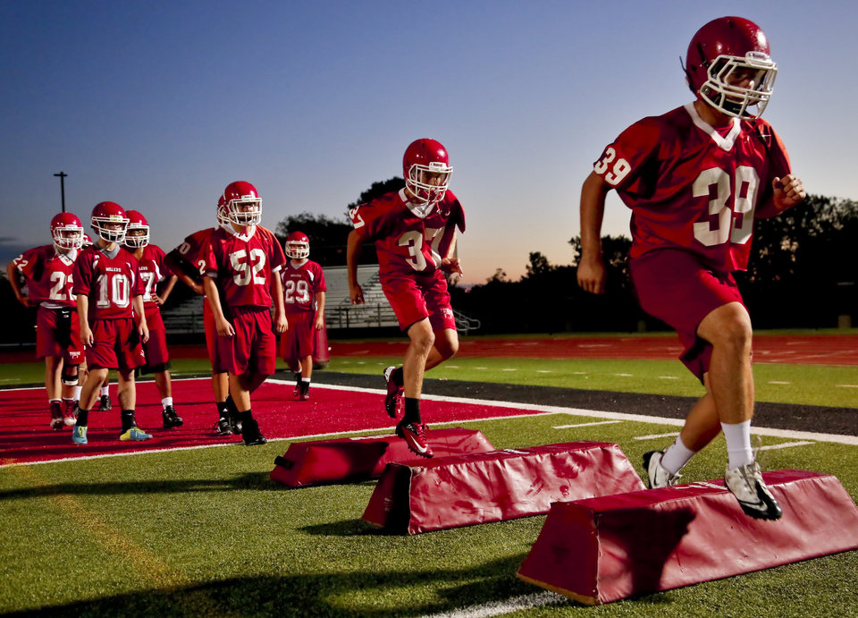 Photo - The Yukon Millers football team led by first year head coach Bill Young take to the field for first day of team practice in Yukon, Okla. on Monday, Aug. 11, 2014. Photo by Chris Landsberger, The Oklahoman