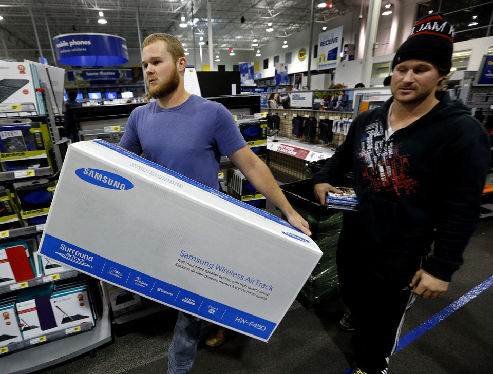 Photo - Brothers Trey and Chance Jones take their selection to the check out counter as shoppers get an early start on Black Friday at Best Buy on Thursday, Nov. 28, 2013, in Norman, Okla.  Photo by Steve Sisney, The Oklahoman