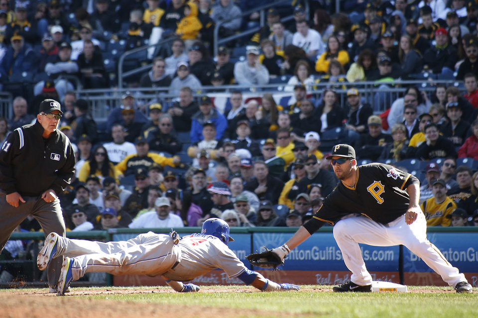 Photo - Pittsburgh Pirates first baseman Travis Ishikawa, right, reaches to tag Chicago Cubs Emilio Bonifacio as he dives back to first on a pickoff attempt in the tenth inning the opening day baseball game on Monday, March 31, 2014, in Pittsburgh. The Pirates won 1-0 in ten innings. Bonifacio was called safe by first base umpire Bob Davidson, left, but the call was overturned on a review requested by manager Clint Hurdle and Bonifacio was ruled out. (AP Photo/Keith Srakocic)