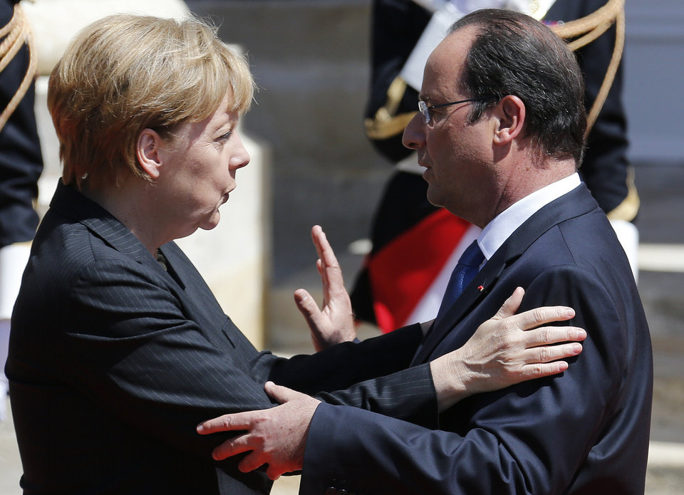 Photo - French President Francois Hollande, right, welcomes German Chancellor Angela Merkel before the official lunch at Benouville castle, in Normandy, France, Friday, June 6, 2014. World leaders and veterans paid tribute on the 70th anniversary of the World War Two D-Day landings to soldiers who fell in the liberation of Europe from Nazi German rule, as host France sought to use the event to achieve a thaw in the Ukraine crisis. (Regis Duvignau, pool)
